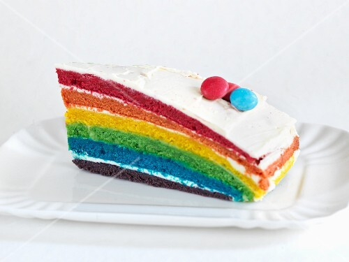A slice of rainbow cake with coloured chocolate beans