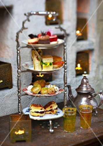 Sandwiches, scones and petit fours on a stand for teatime in a restaurant