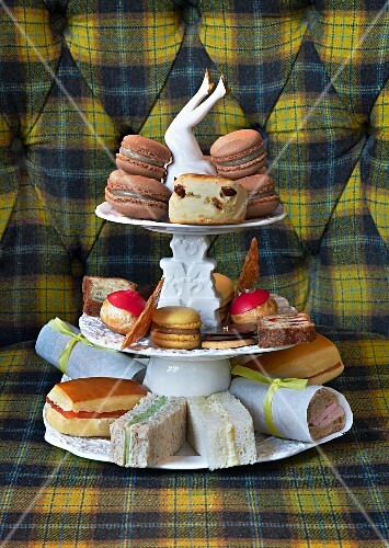 Sandwiches and macaroons on a vintage cake stand for teatime