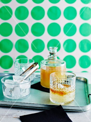 Iced tea in a bottle and glass with a dish of ice cubes and a pair of tongs on a tray
