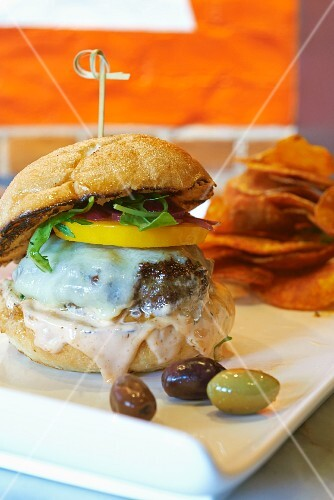 A cheeseburger with melted cheese and yellow tomatoes served with crisps and olives