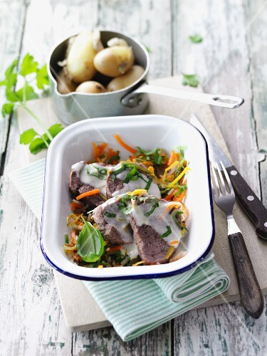 Steamed veal medallions on a bed of herbs and vegetables