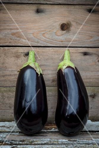 Two aubergines on a wooden surface