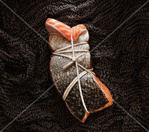 A trussed up piece of salmon on a chain mail shirt