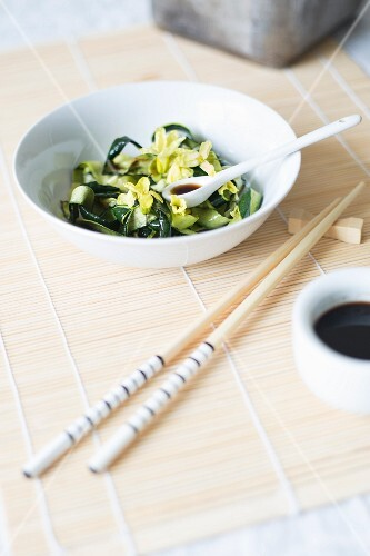 Courgette spaghetti with flowers on a bamboo mats with chopsticks (Asia)