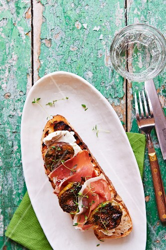 Crostino topped with salmon mousse, ham and figs