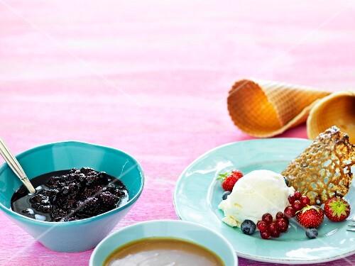 Vanilla ice cream with berries and a liquorice wafer served with ice cream cones, berries and caramel sauce