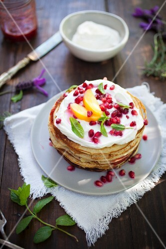 A pancake tower with ricotta and pomegranate seeds