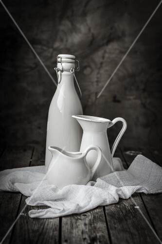White jugs and a flip-top bottle on a muslin cloth
