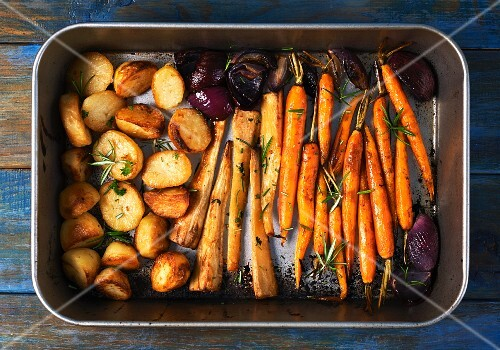 Roasted root vegetables and red onions in a roasting tin