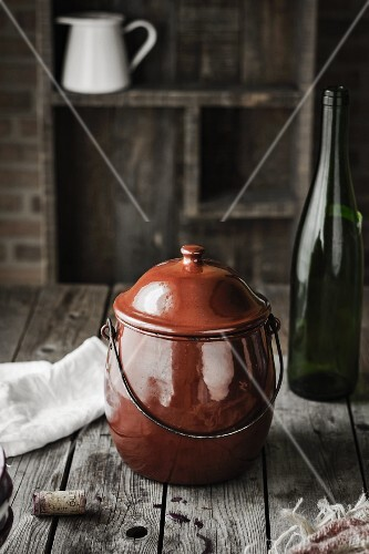 An old cooking pot and an empty wine bottle on a wooden table