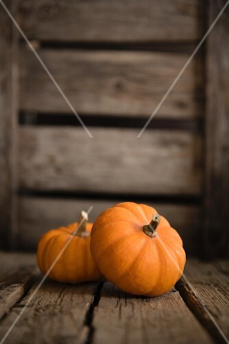 Two small pumpkins on a wooden surface