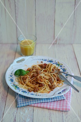 Spaghetti Bolognese on porcelain plate with a basil leaf and a glass of orange juice