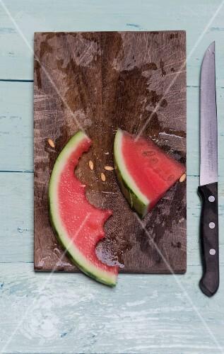 A half eaten slice of watermelon on a wooden board