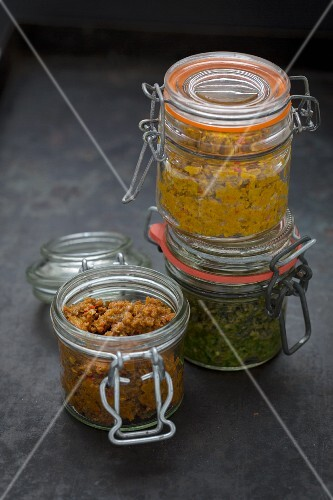 Red, yellow and green curry paste in flip-top jars