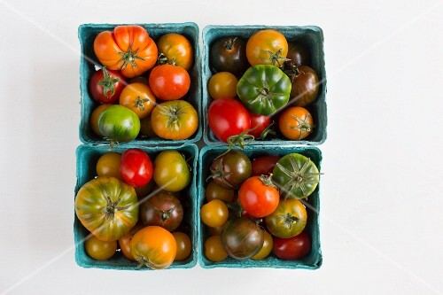 Heirloom tomatoes in blue cardboard punnets