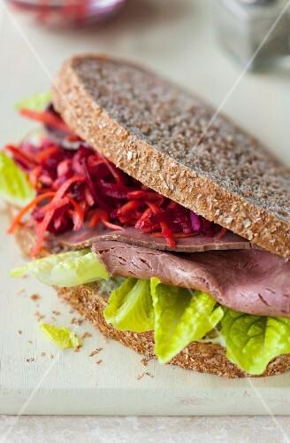 A roast beef sandwich, coleslaw and lettuce