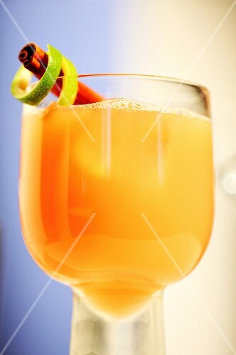 An orange drink garnished with a cinnamon stick and lime zest