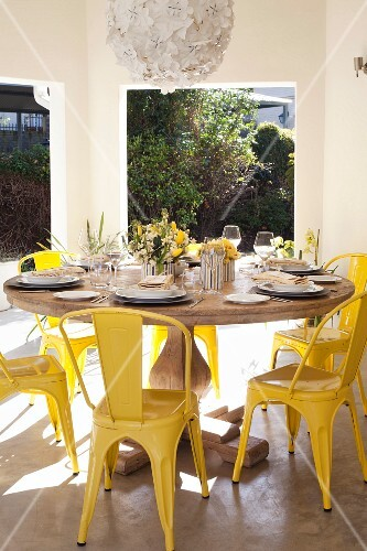 Festively set, round wooden table and yellow vintage chairs on roofed terrace