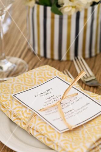 Menu tied to folded napkin with ribbon
