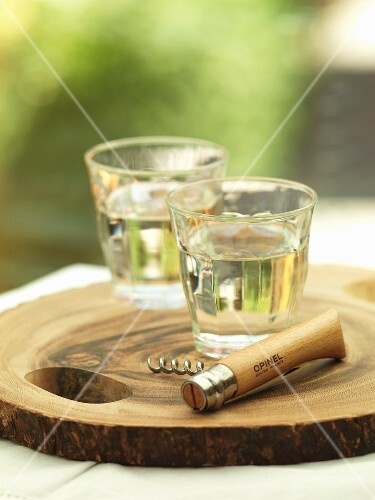 Glasses of white wine and a corkscrew on a wooden board