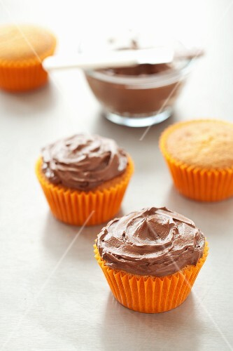 Cupcakes with chocolate frosting in orange paper cases