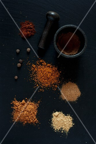Piles of various ground spices on a black surface with a pestle and mortar