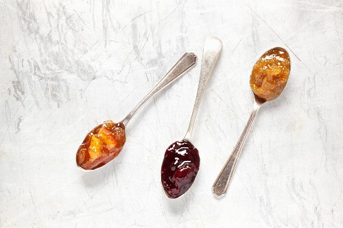 Three antique jam spoons on a metal surface