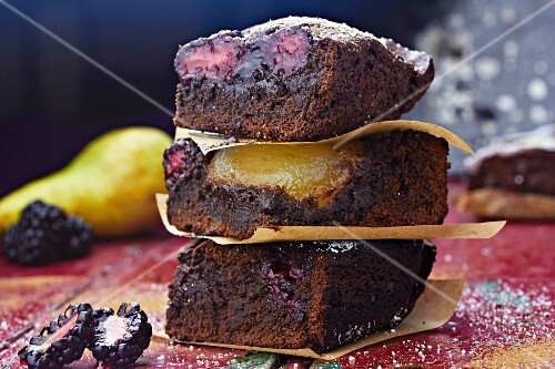 A stack of three slices of chocolate and pear cake with blackberries