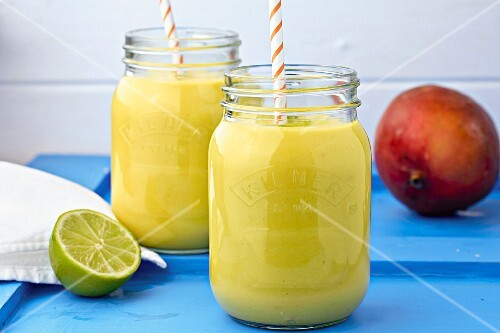 Mango and lime cocktails in jars with straws