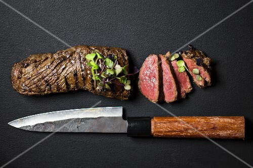 Sliced steak with shiso cress and a Japanese knife on a black surface