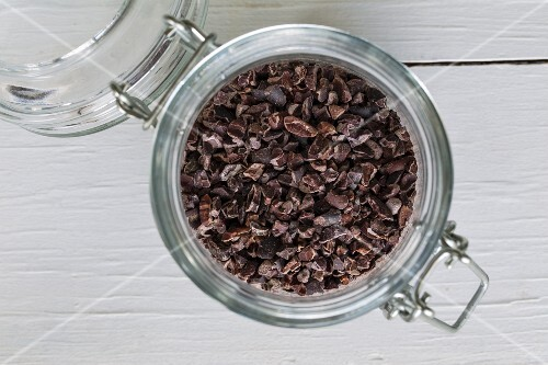 Cocoa nibs in a flip-top jar on a white wooden surface