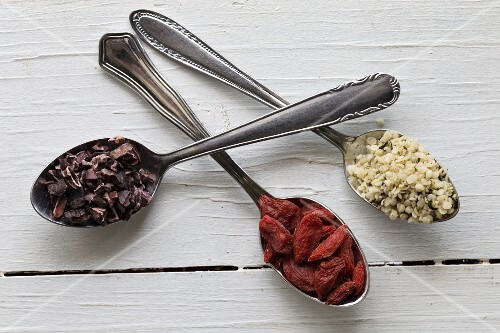 Cocoa nibs, goji berries and hemp seeds on silver spoons on a white wooden surface