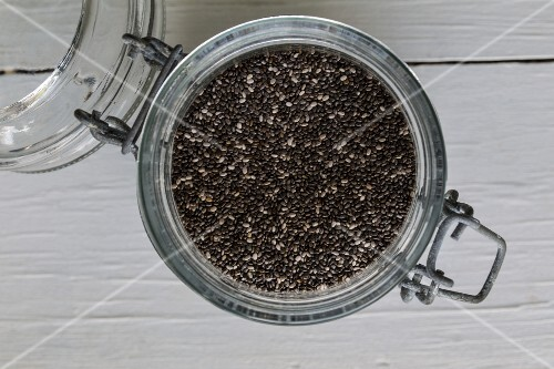 Chia seeds in a flip-top on a white wooden surface