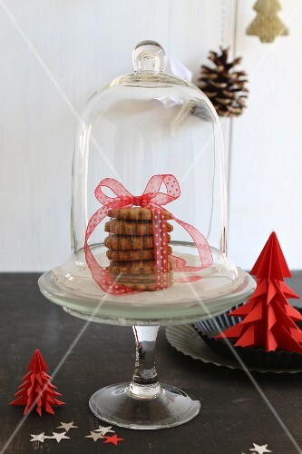 Stack of Christmas biscuits tied with ribbon under glass cover next to red paper Christmas tree