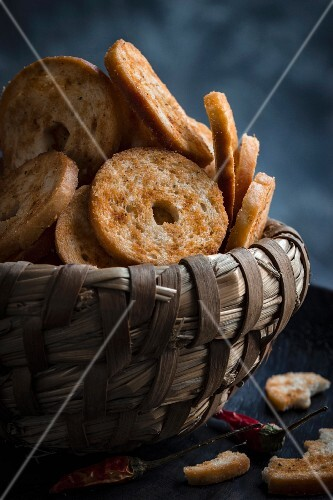 Bread chips in a bread basket with chillis against a dark background