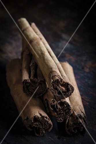 A stack of cinnamon sticks on a dark wooden table