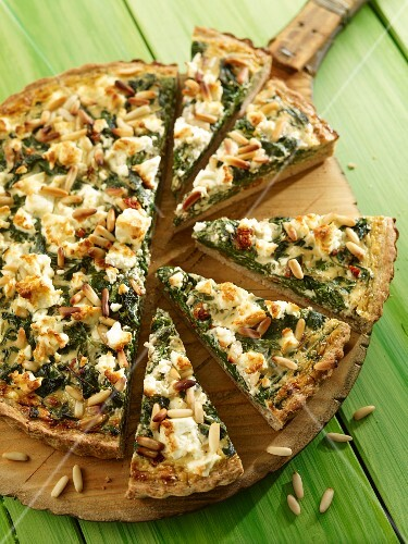 Spelt wholemeal quiche with spinach and pine nuts, sliced