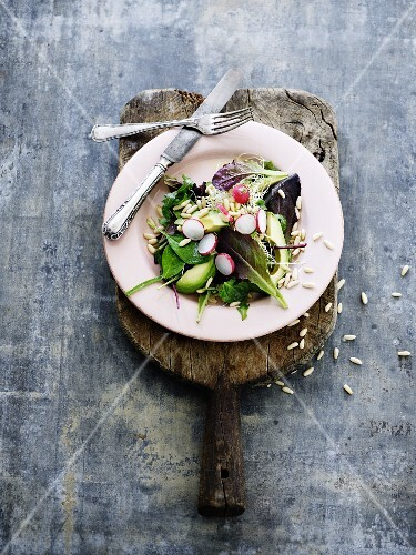 Mixed leaf salad with avocado, radishes and pine nuts