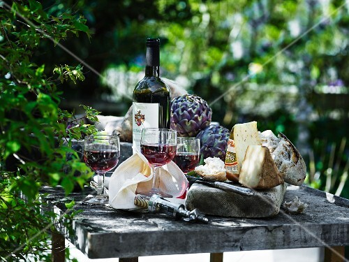 An arrangement of red wine, cheese and bread