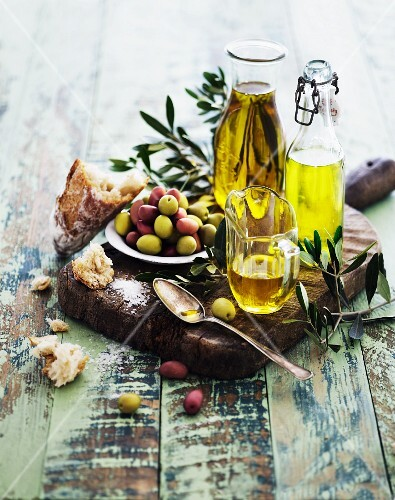 An arrangement of oils with olive sprigs, olives and bread