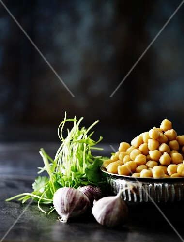 Chickpeas in a metal bowl with garlic and coriander next to it