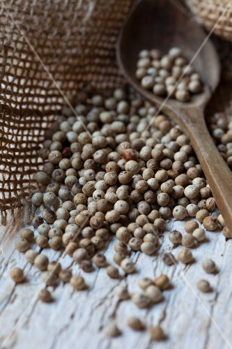 Black peppercorns with a wooden spoon