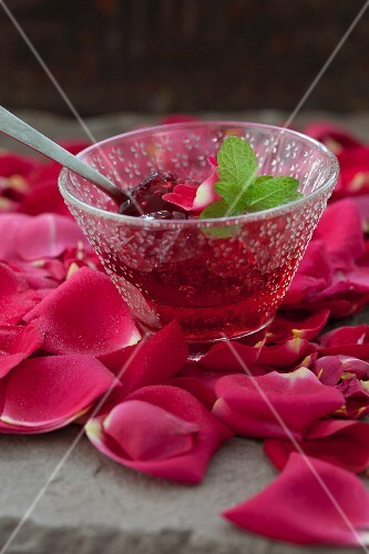 Rose jelly with lemon balm in a glass bowl on rose petals