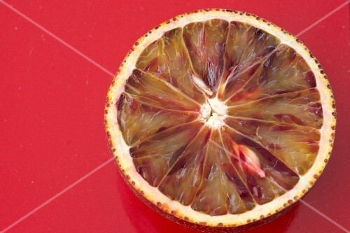 Half a blood orange on a red surface