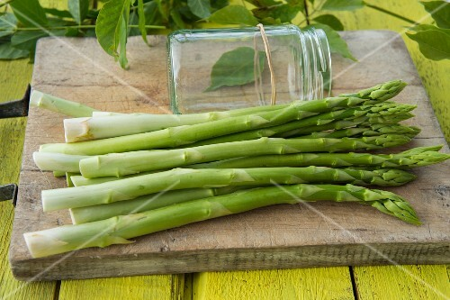 Green asparagus on a wooden board next to a screw-top jar with a rubber band