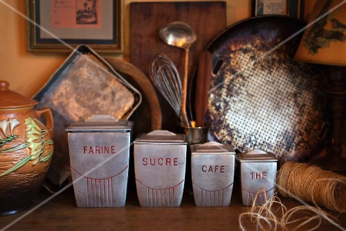 Old-fashioned, metal storage jars in a rustic kitchen