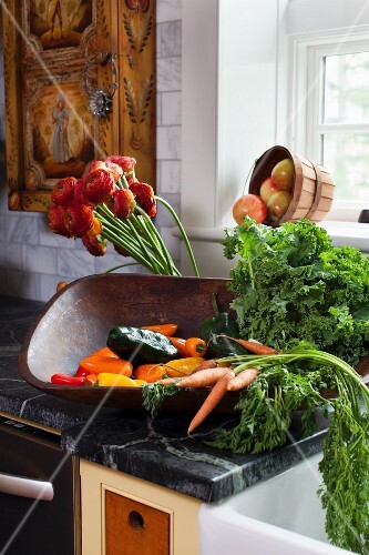 Fresh vegetables in a wooden bowl on a counter in a farmhouse kitchen