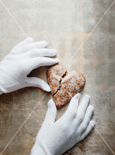 Gloved hands holding a heart-shaped gingerbread biscuit