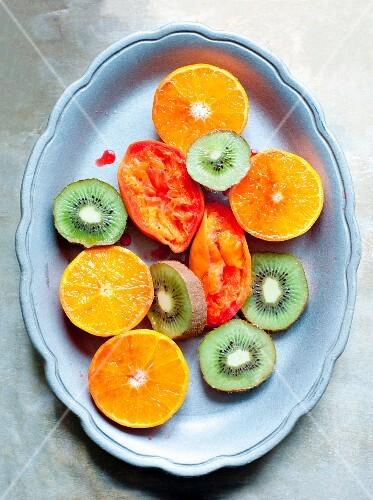 Kiwi slices, halved oranges and juiced blood oranges on a plate